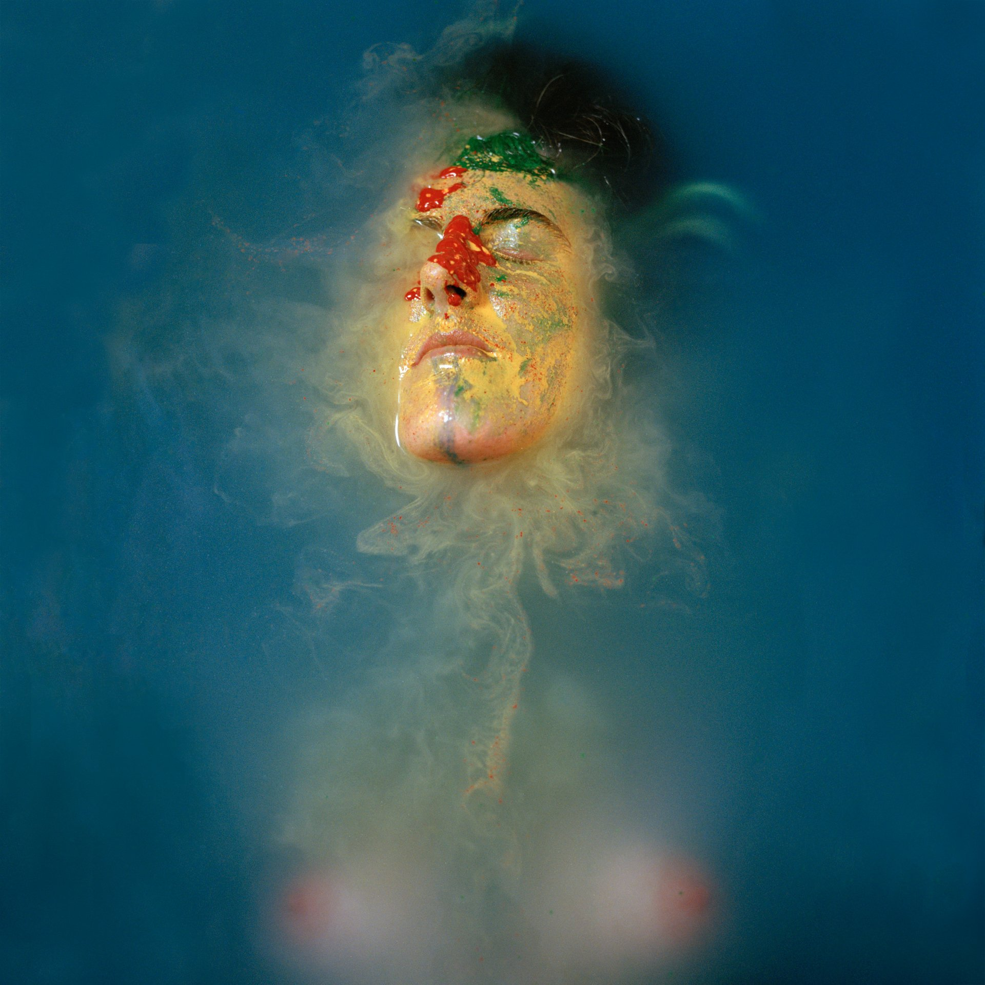 Hannah Laycock in a bath of water and blue and red paint for the 'Perceiving Identity' project about multiple sclerosis