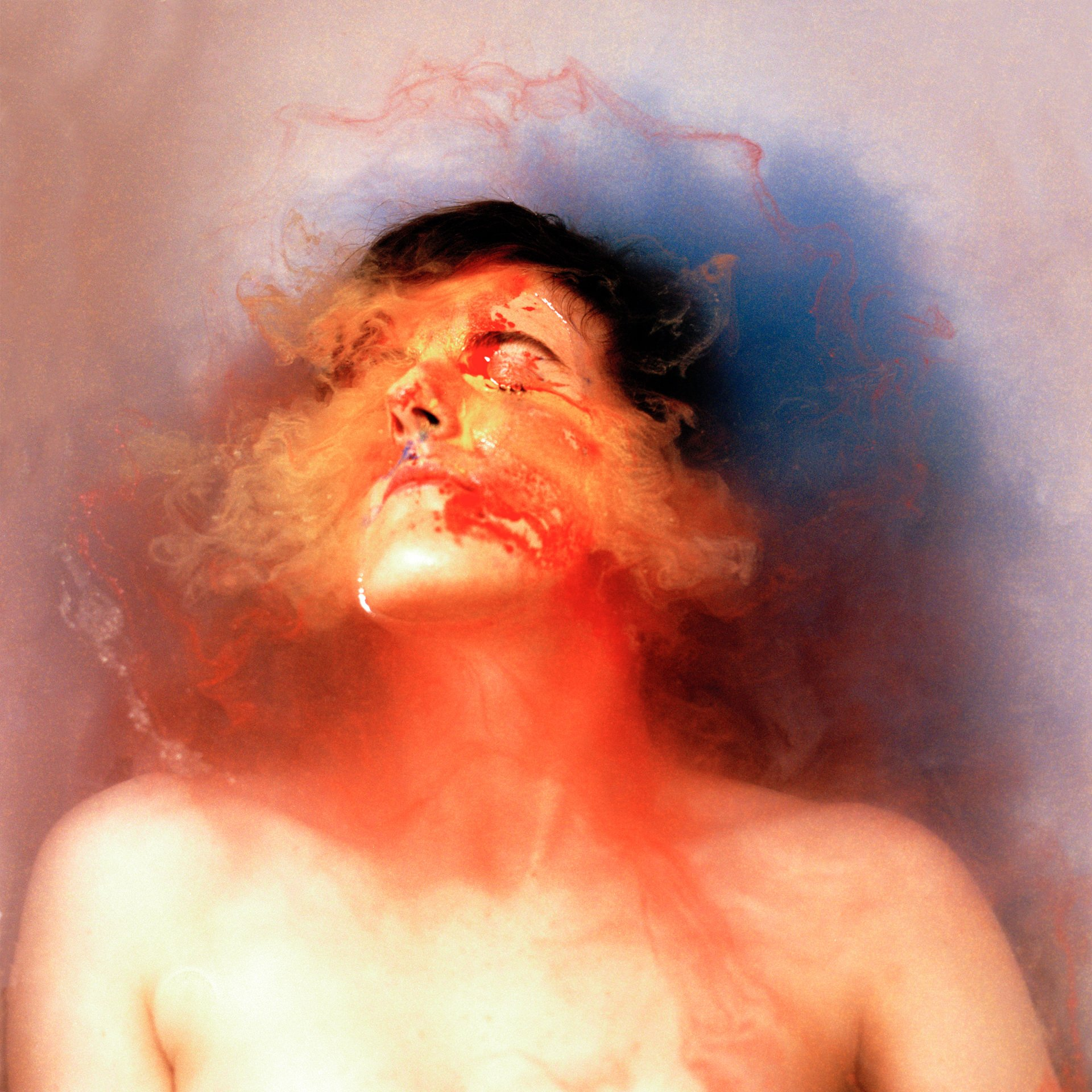Hannah Laycock in a bath of water and blue, red and yellow paint for the 'Perceiving Identity' project about multiple sclerosis