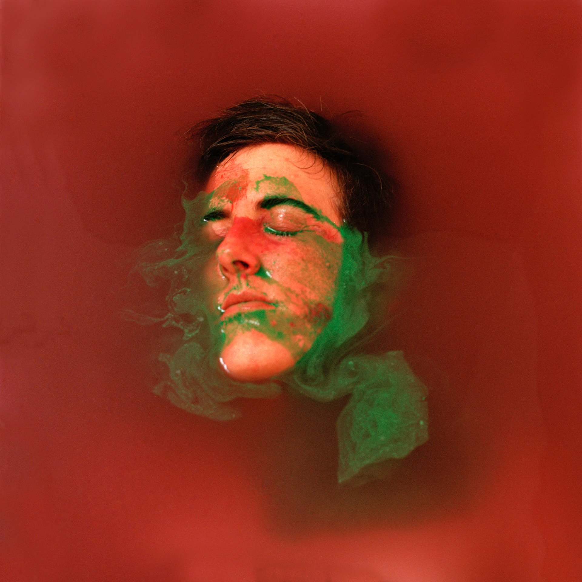 Hannah Laycock in a bath of water and red and green paint for the 'Perceiving Identity' project about multiple sclerosis
