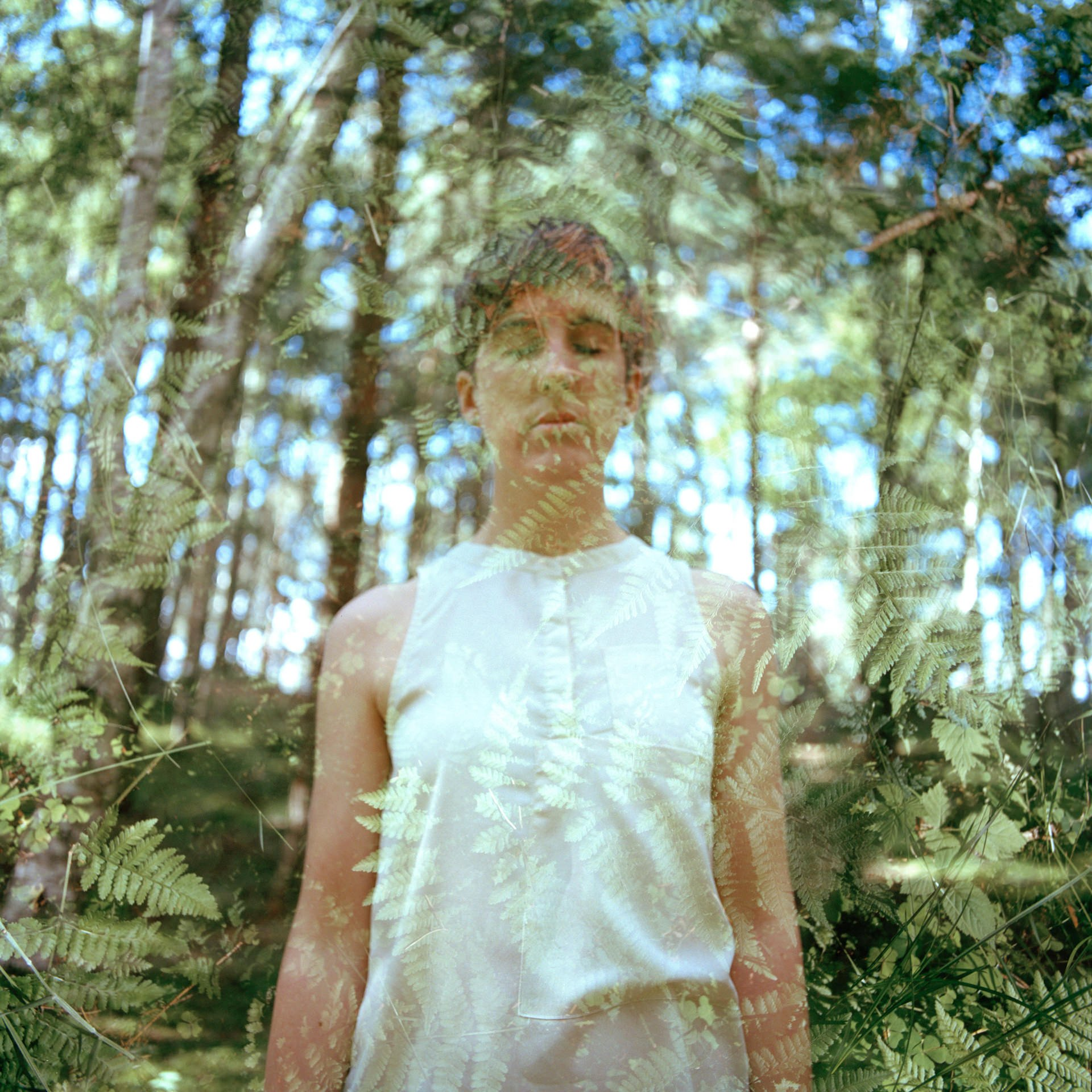 Hannah Laycock double exposure self-portrait with fern leaves taken in Culbin forest, Scotland, wearing a cream, sleeveless top