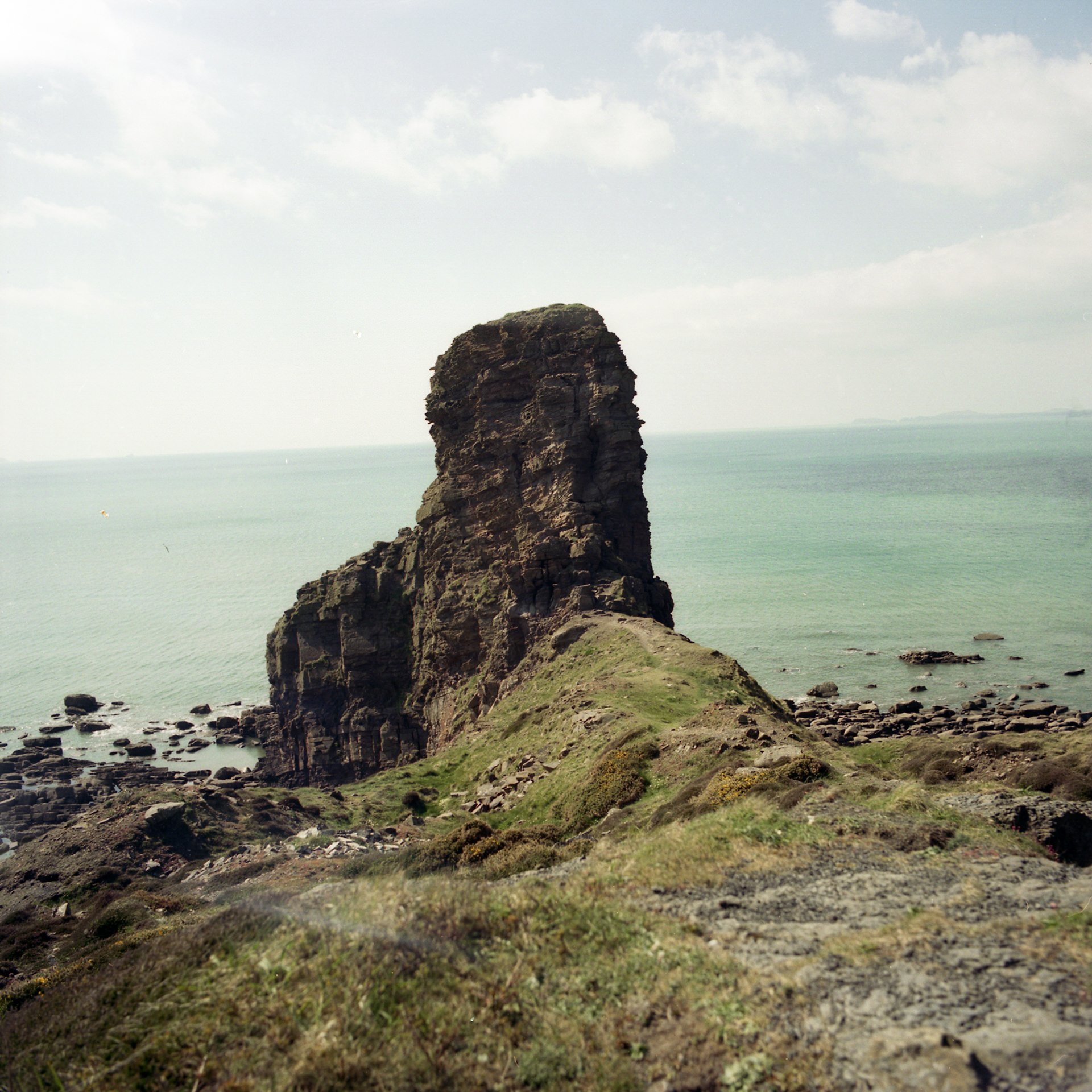 A rock pertruding up towards the sky on a green grassed cliff edge