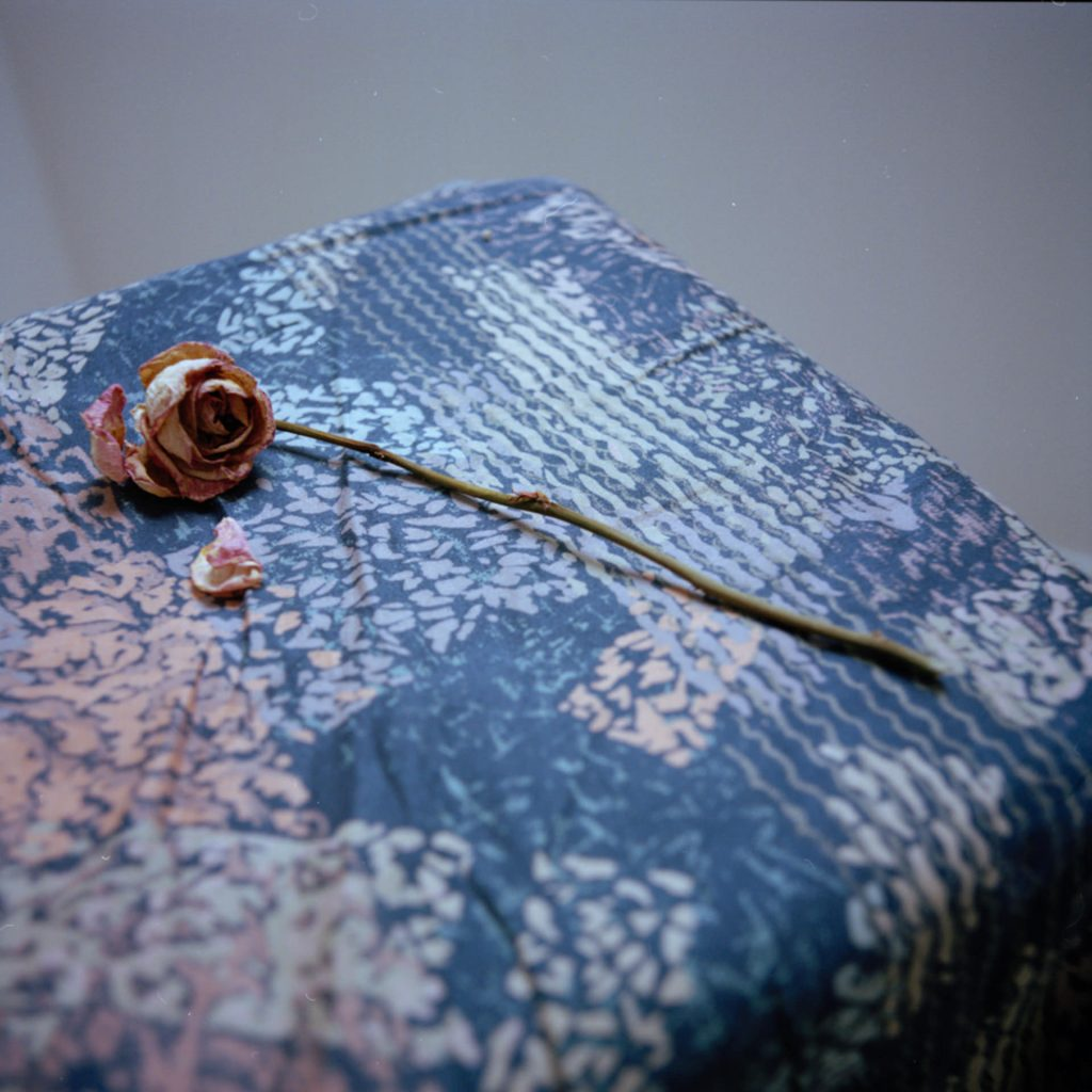 A dried pink rose, with stem, lying on a small table with a blue and pink abstract table-cloth against a white wall