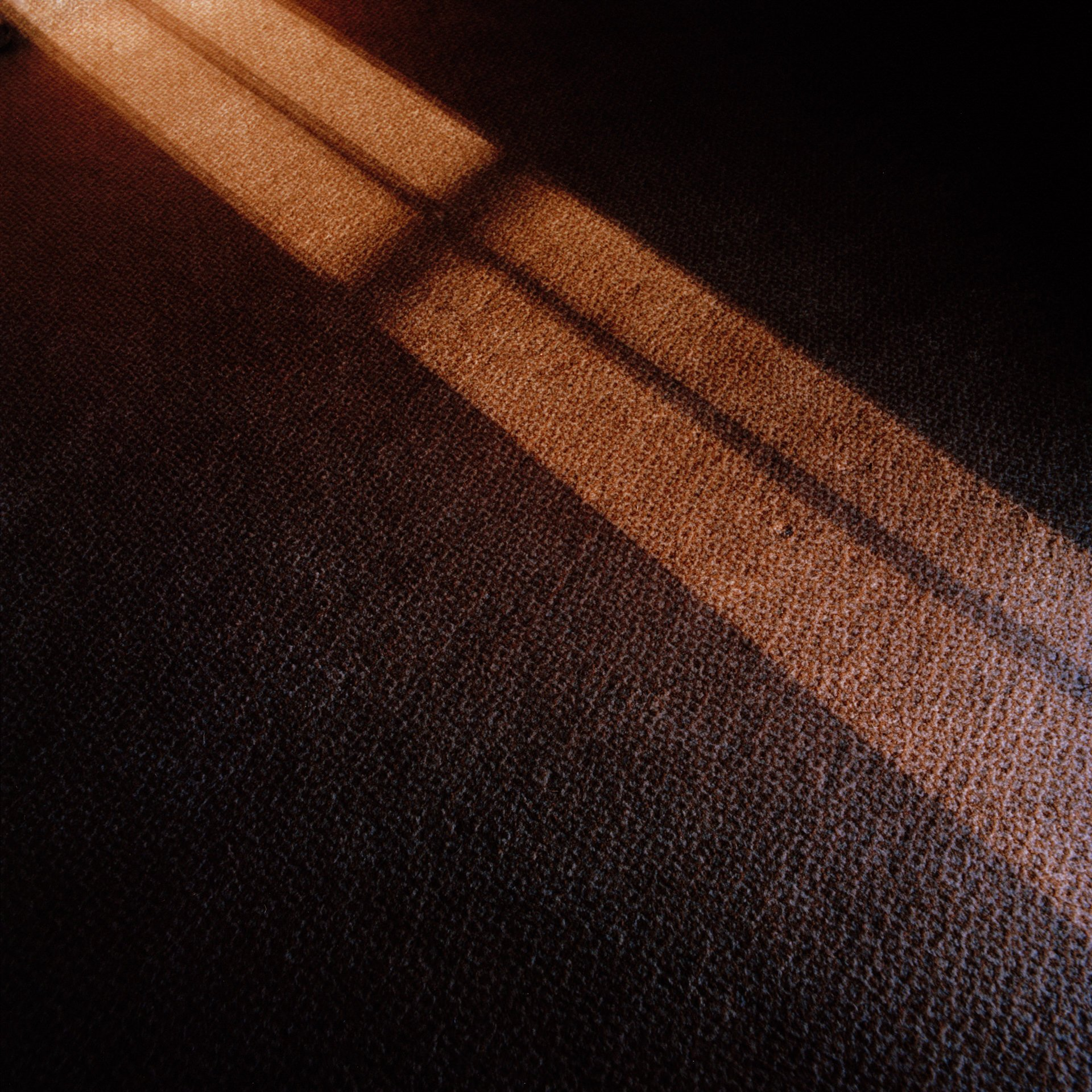 Golden light reflects a window onto brown carpet that appears like a holy cross