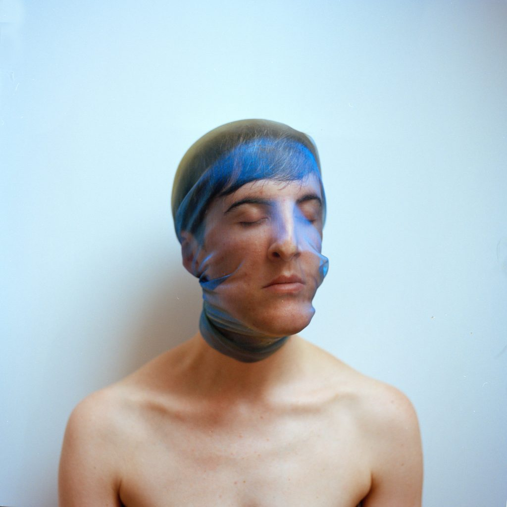 A portrait of Hannah Laycock with bare shoulders and blue voile fabric wrapped around her head