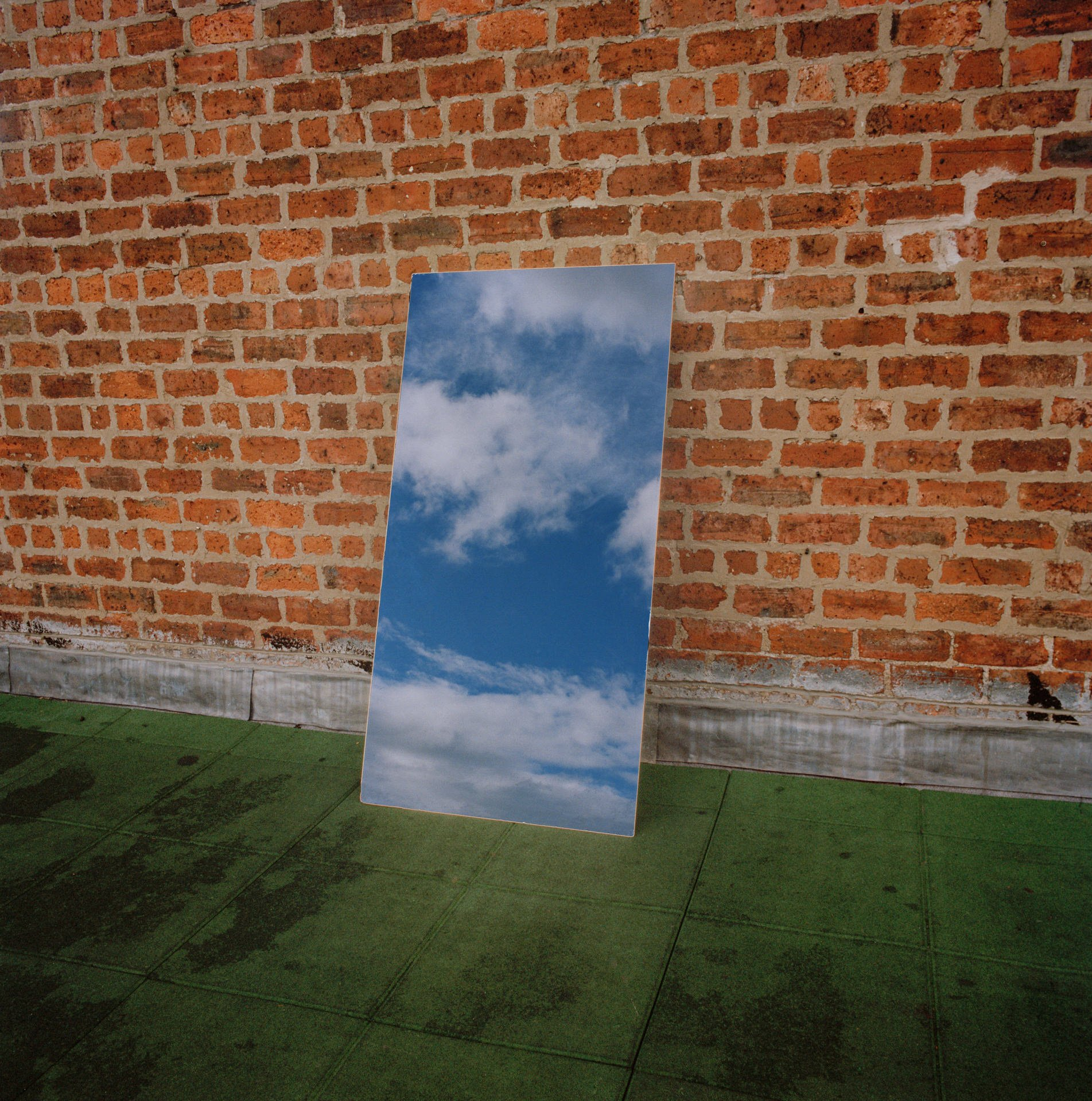 A tall, portrait mirror leans against a red brick wall and sits on astro turf, reflecting the blue sky and white puffy clouds