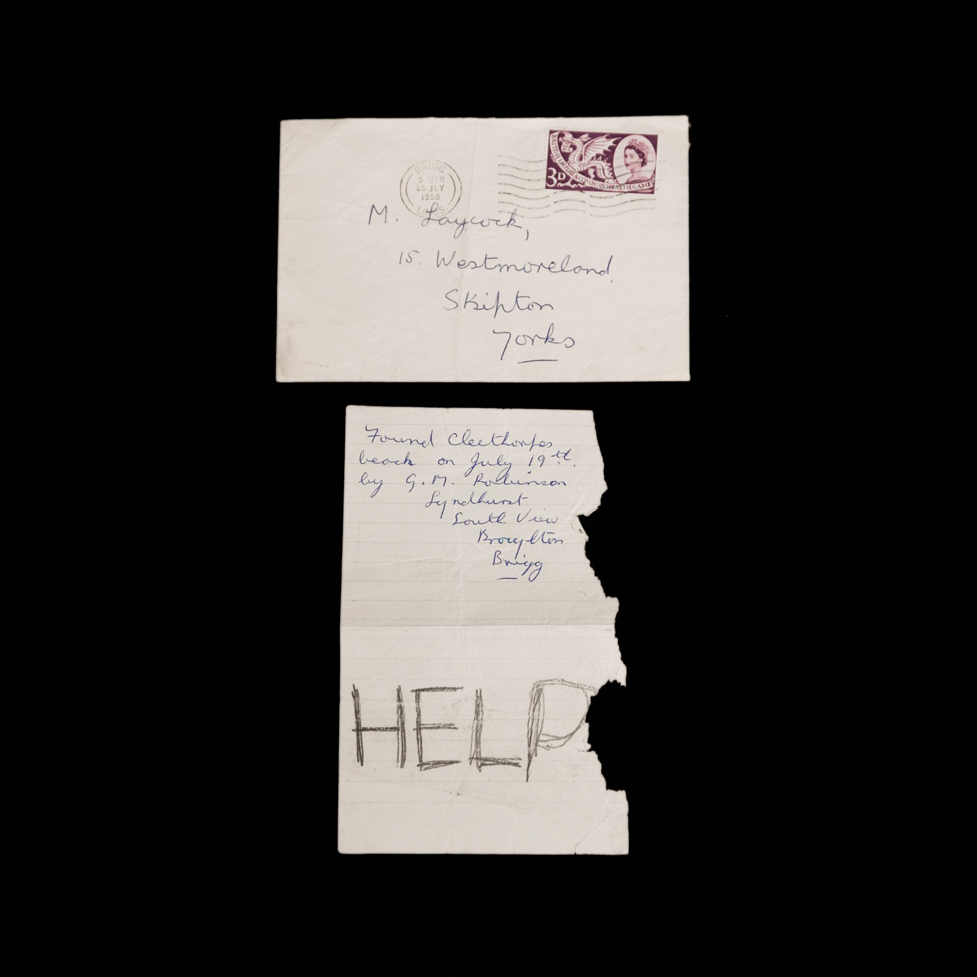 A letter with the word 'HELP' scribed on the page, along with a stamped envelope with an address written on it as part of 'The Fundamental Makings of A Solitary Voyager' archive