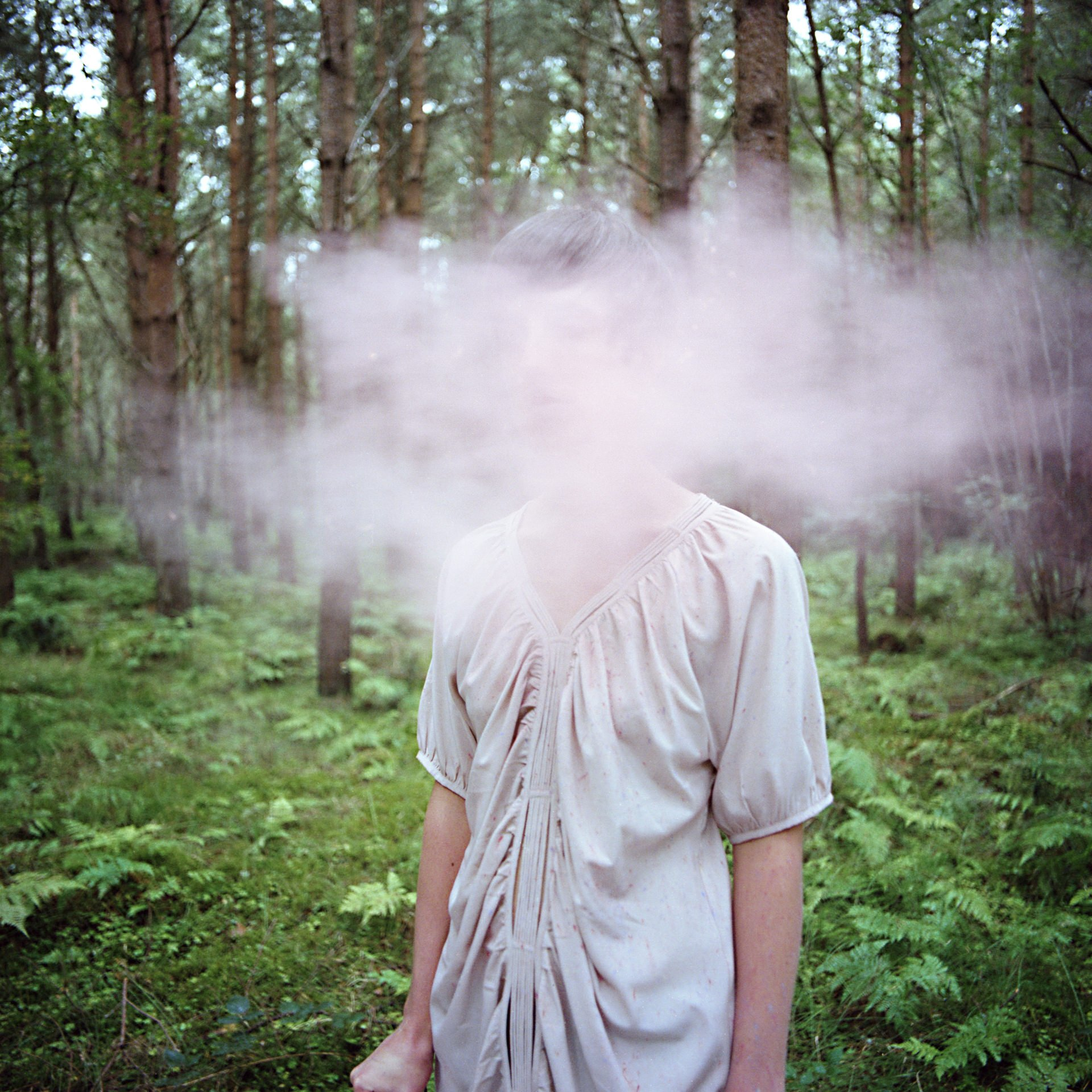 Hannah Laycock pictured in a forest with dust covering her face for the Perceiving Identity project about Multiple Sclerosis