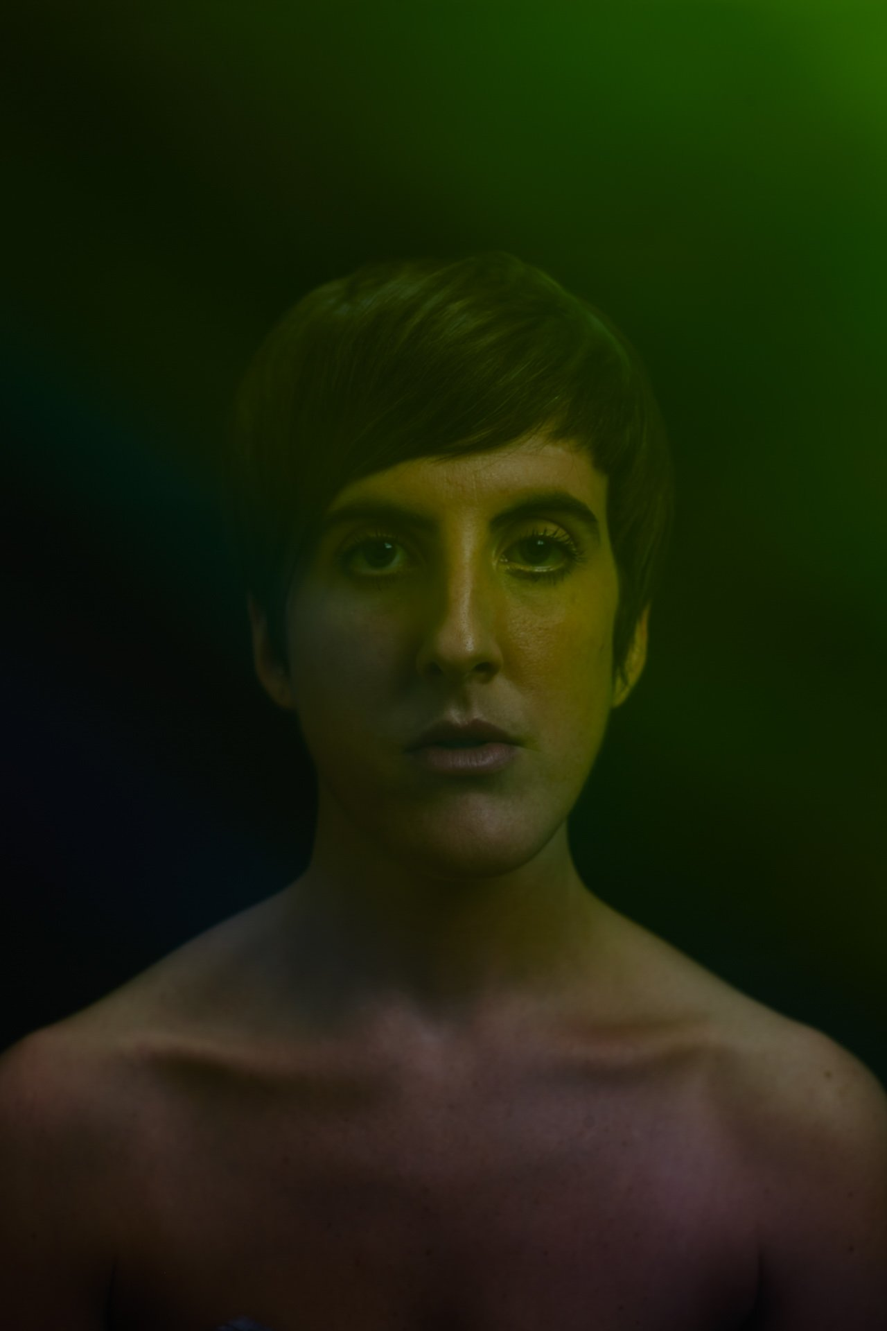 Darkly lit portrait of Hannah Laycock against a black backdrop with a spectrum of colour across her skin