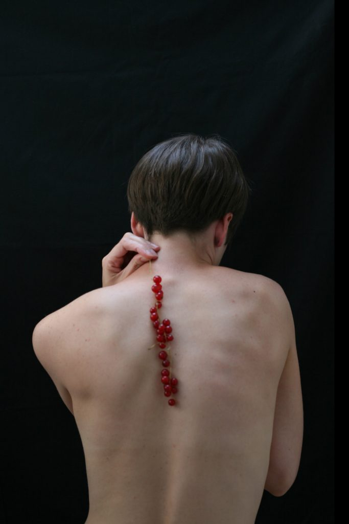 Naked portrait of Hannah Laycock against a black backdrop with her back to the camera holding a bunch of redcurrent berries and hanging down her spine