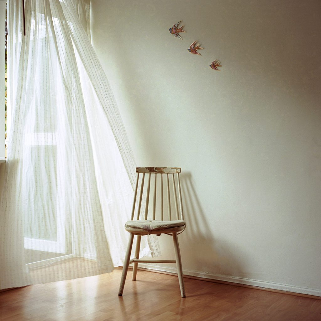 White walled room with ornamental swallows hanging on the wall, wooden laminate flooring and a chair stands next to a doorway with a lightweight cotton curtain blowing in the wind