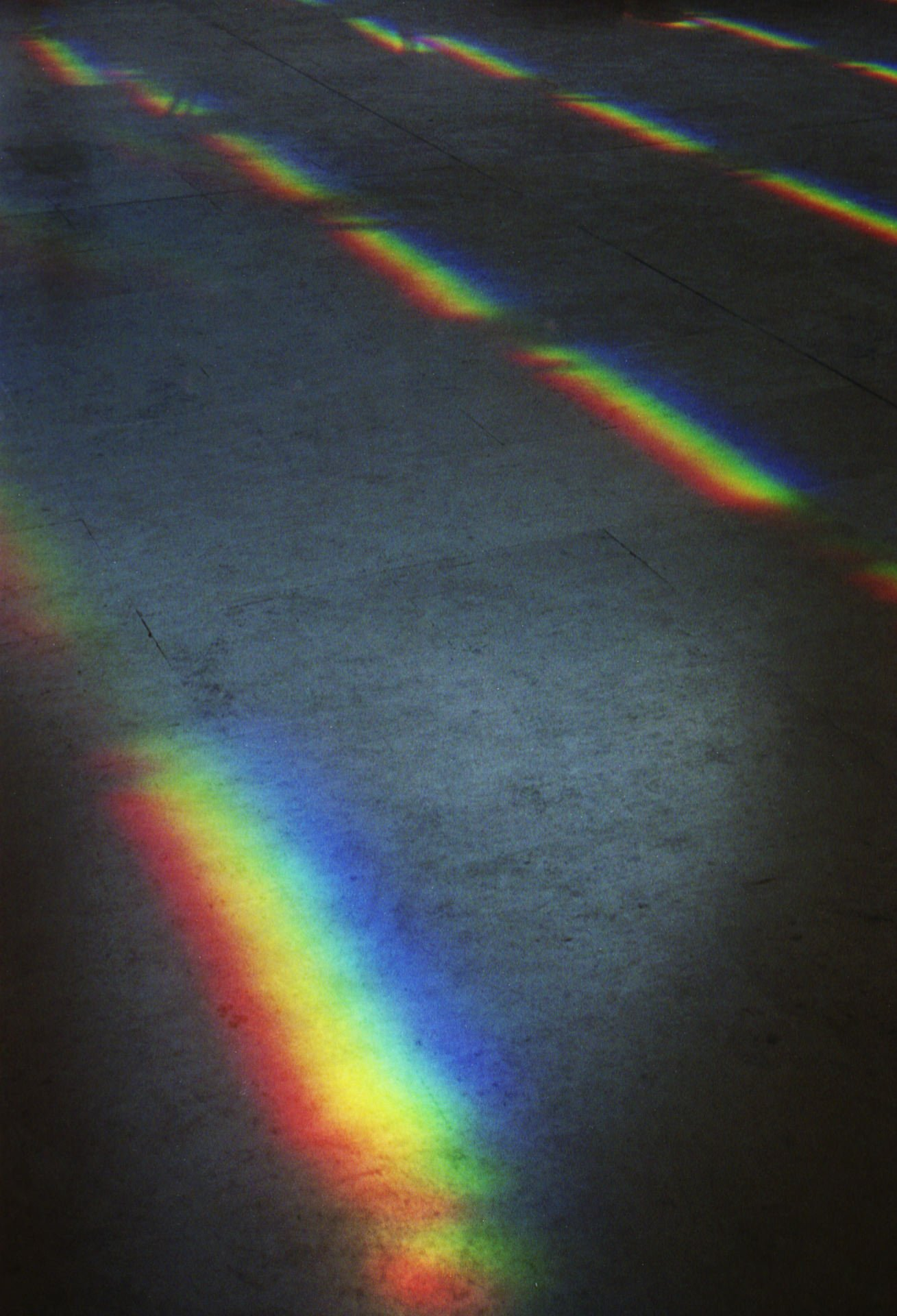 On a concrete floor a reflected spectrum of colour shines on the floor