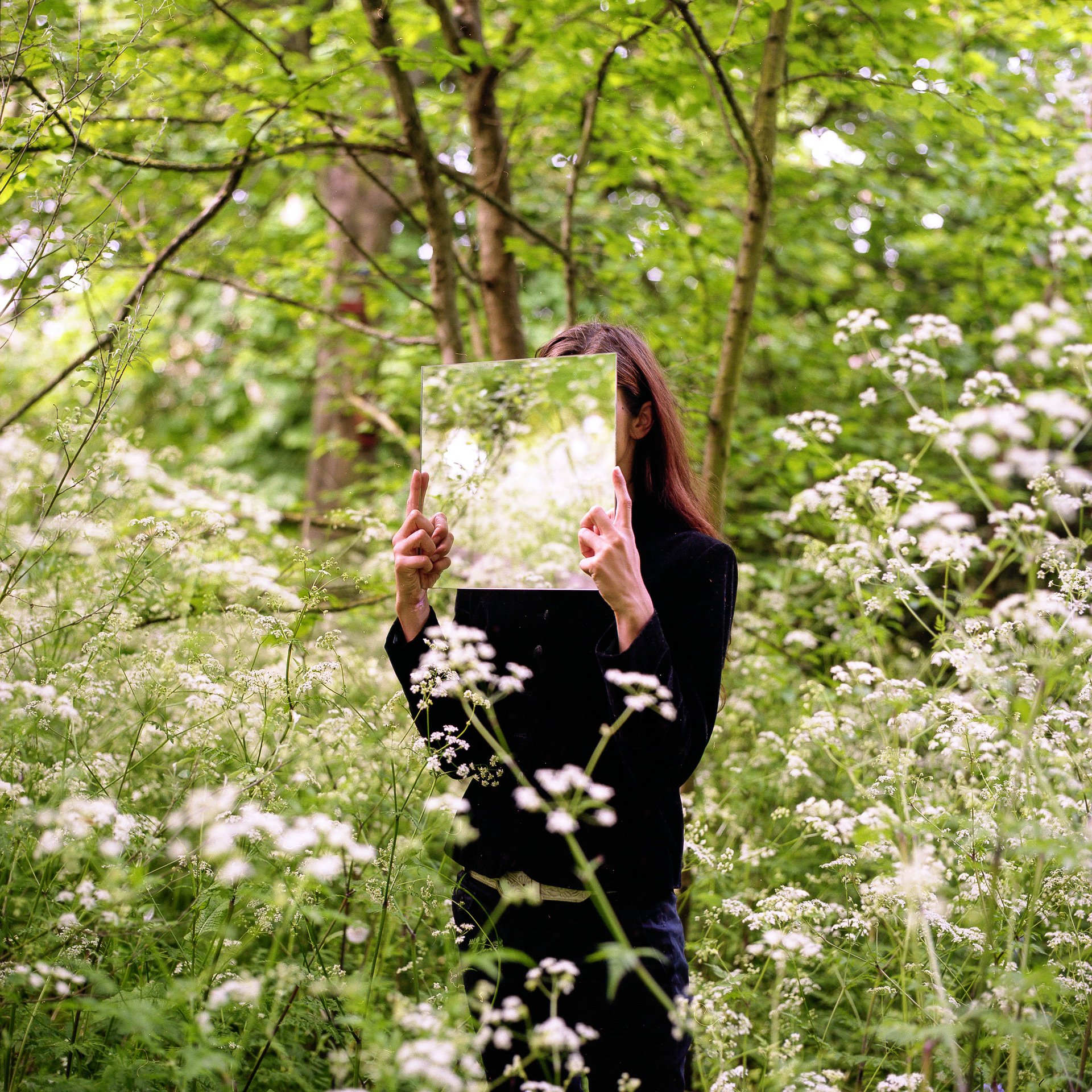 Guna stood in the middle of a park holding a square mirror in front of her face, that reflects the plant life around her, surrounded by blossoming plants with white flowers and trees in the background