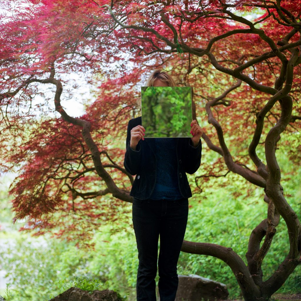 Kayla stood in a park holding a square mirror in front of her face, under a Japanese tree with red leaves
